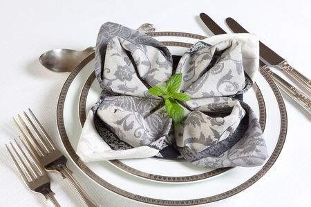napkins: Ornate fancy napkins on a festive dinner table in grey