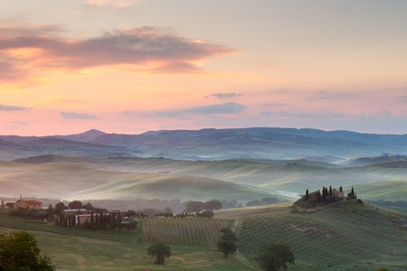 farmhouses: Misty morning in the Tuscan hills at San Quirico dOrcia with view on Belvedere villa Stock Photo