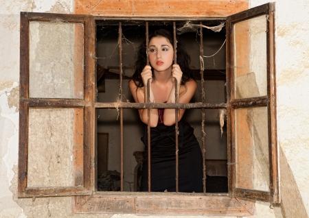 gefangener: Staring Frau schaut aus einem Fenster eines verlassenen Gefängnis