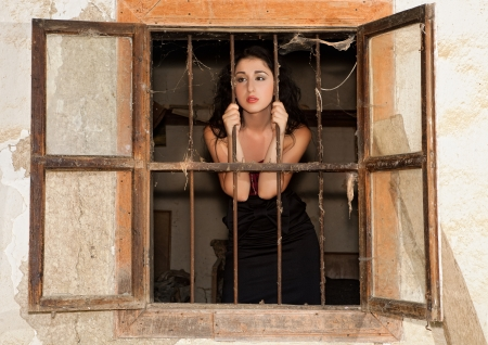Staring woman looking out of a window of a derelict prison photo