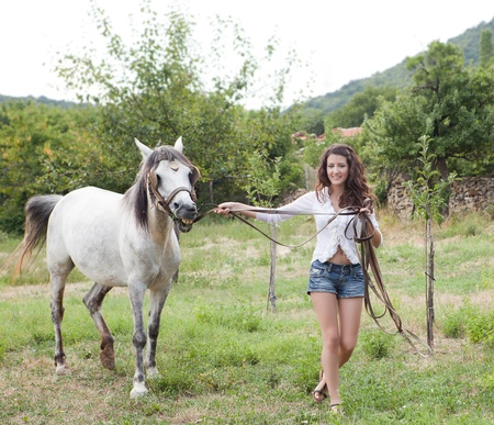 Attractive young woman walking with a farm mare photo