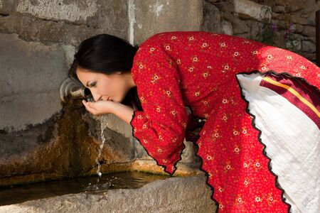 bulgarian ethnicity: Beautiful woman in traditional national bulgarian costume drinking at a well in the old village of Jeravna Stock Photo