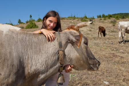 Young girl looking after the cows in the Bulgarian mountains photo