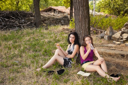 Two young women relaxing in the woods with an apple and a drink photo