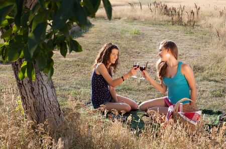 Happy young women tasting wine during a picnic in golden evening light photo