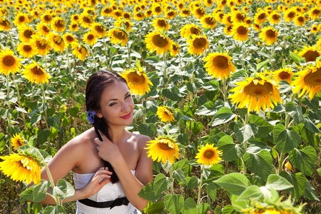 Blue flowers in the hair of a young woman in a sunflower field in Bulgaria photo