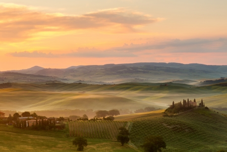 Tuscan villa in the fog on a misty sunrise morning in San Quirico d Stock Photo