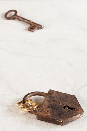 Rusty old padlock with key and wedding rings photo