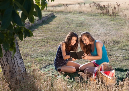 Young women sharing a book during a picnic photo