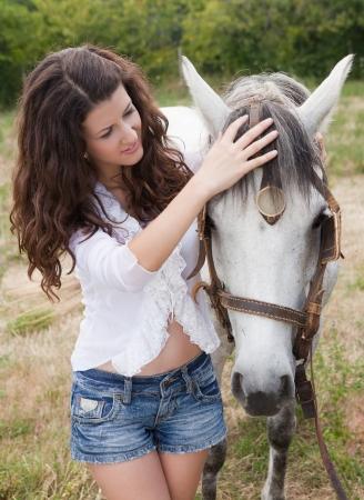 merrie: Mooi meisje de zorg voor haar paard in een weide Stockfoto