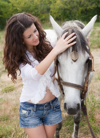 Pretty girl caring for her horse in a meadow photo