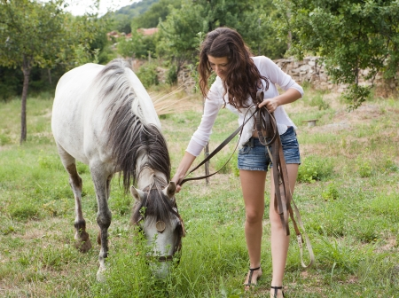 Young woman walking with a farm horse in a meadow photo
