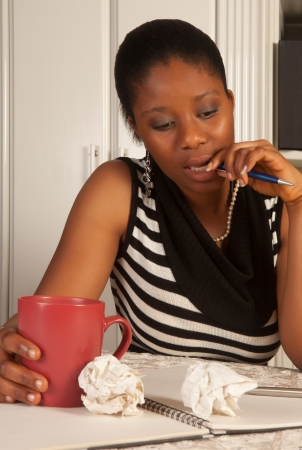 Thinking african woman writing a letter at home photo