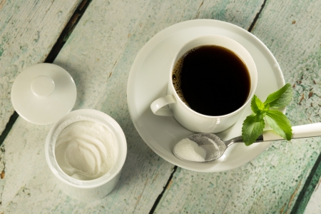 White stevia natural sweetener in powder form and a cup of coffee photo