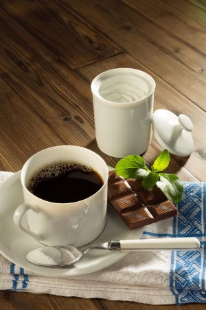 Powder stevia and stevia chocolate next to a cup of coffee without sugar photo