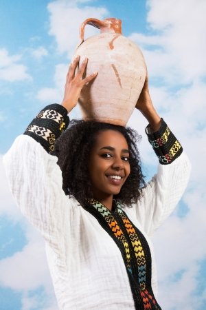Young African Ethiopian woman carrying a jug or stone pitcher photo