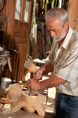 craftsmanship: Skilled carpenter at work with hammer and chisel in an old shed