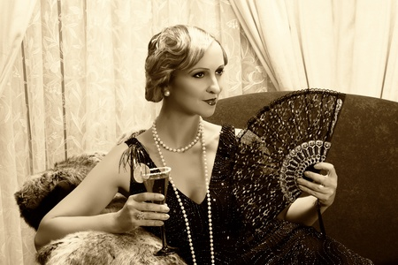 Sepia image of a vintage twenties lady with cocktail and lace fan photo
