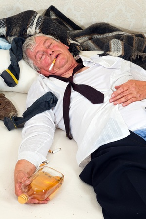messy clothes: Drunk man lying in a messy bed Stock Photo