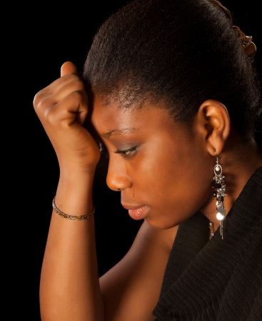 ghanese: Crying young African Ghanese woman against a black background