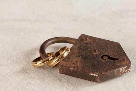 wedlock: Wedding rings locked up by a rusty old padlock