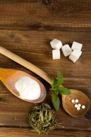 Various forms of stevia natural sweetener plus real sugar lumps on a wooden table photo