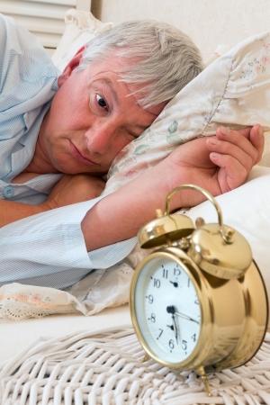 Ringing alarm clock and sleepy pensioner looking at it photo