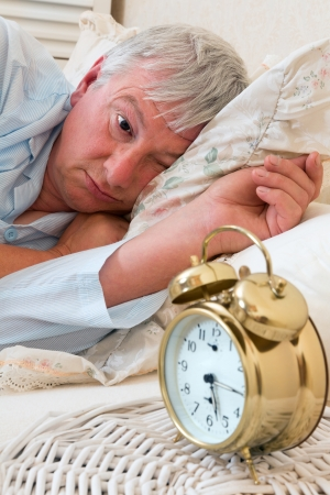 Ringing alarm clock and sleepy pensioner looking at it Stock Photo - 14747383