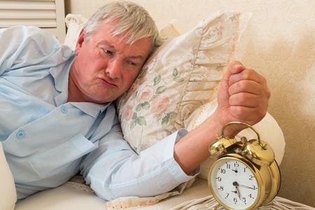 grumpy old man: Bad tempered grumpy old man in bed Stock Photo