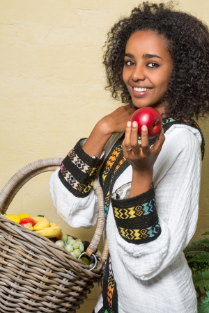Smiling Ethiopian woman in traditional costume offering an apple photo