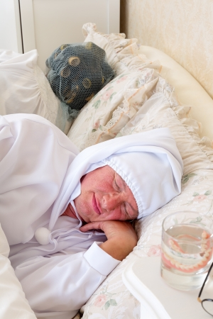 Eldery couple in vintage nightwear asleep in bed photo