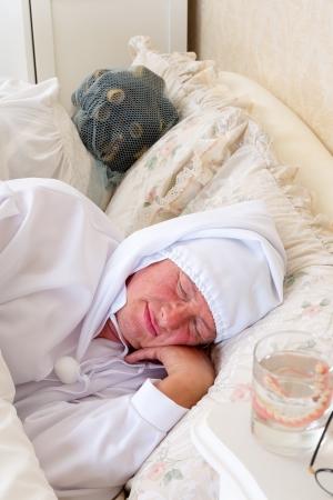 Eldery couple in vintage nightwear asleep in bed photo
