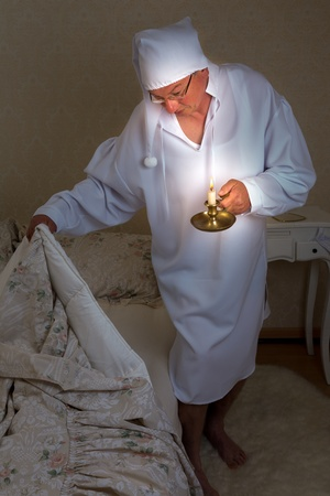 Vintage mature man going to bed with a candle photo
