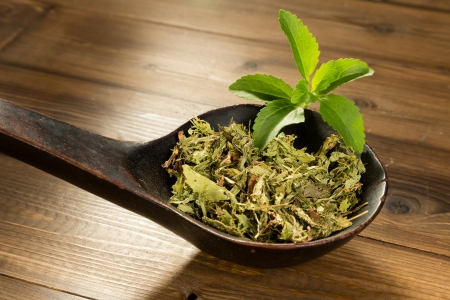 supplements: Wooden spoon filled with dried natural sweetener stevia leaves