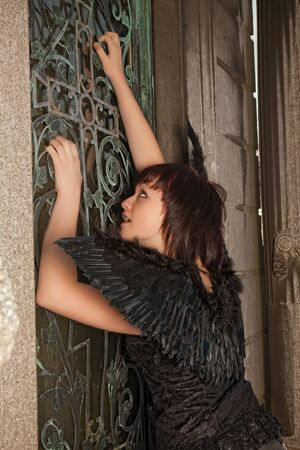 Gothic woman with black wings knocking on an antique door in a cemetery Stock Photo - 14903762