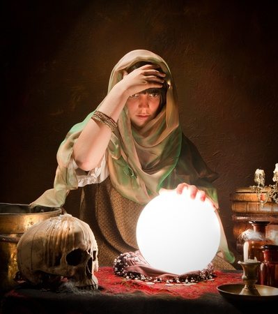 Crystal ball illuminating a young fortune telling gypsy photo