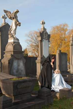Young widow in Victorian dress sitting on a tombstone photo