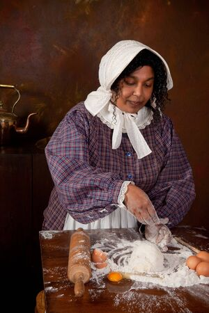 Vintage scene of a colonial woman kneading dough in an antique kitchen photo