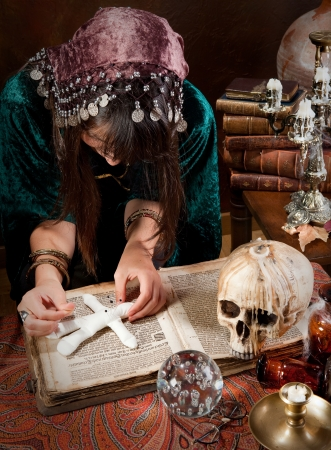 spell: Voodoo gypsy putting needles in a doll casting a spell or curse on it Stock Photo