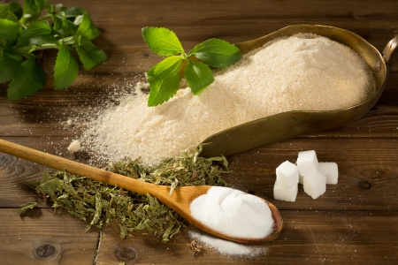 dietary supplements: Crystal sugar and lumps together with powder and dried stevia natural sweetener on a wooden table Stock Photo