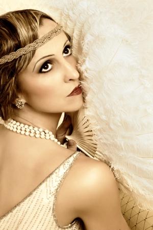 headbands: Retro dama posando con ventilador antiguo y venda vestido flapper Foto de archivo