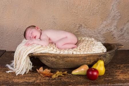 sleeping kid: Sleeping newborn baby of 11 days old in a grunge wooden dough bowl