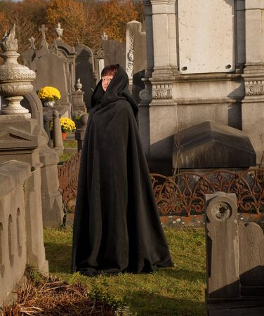 widow: Widow with victorian cape visiting a very old graveyard
