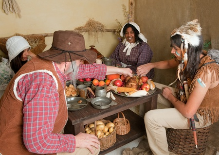 Reenactment scene of the first Thanksgiving Dinner in Plymouth in 1621 with a Pilgrim family and a Wampanoag Indian Stock Photo - 15275983