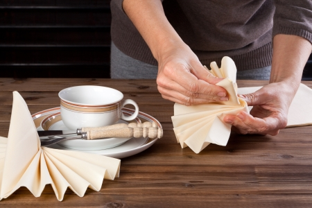 paper folding: Paper napkins being folded on a table for lunch Stock Photo