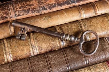 Large rusty key lying on weathered old books Stock Photo - 15407207
