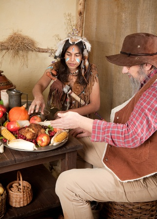Reenactment scene of the first Thanksgiving Dinner in Plymouth in 1621 with a Pilgrim family and a Wampanoag Indian Stock Photo - 15411849