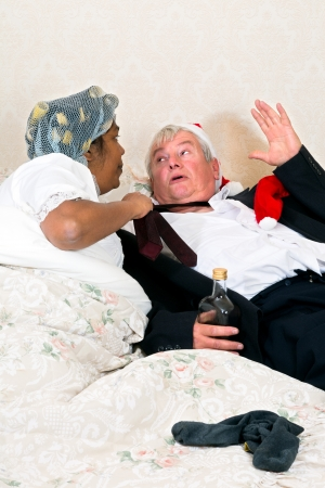 Funny scared drunken husband with his angry wife photo