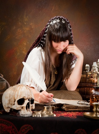 Halloween witch writing in the book of shadows (the book is 300 years old, no copyright problems) photo