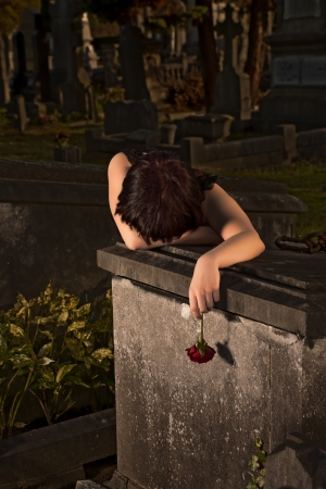 luto: Noche tirada de una mujer gótica joven llorando en una tumba